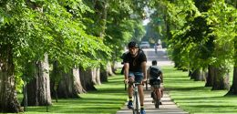Photograph of two men riding opposite directions on campus bike path while sunlight streams between trees.