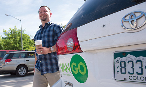 Photograph of a smiling man with a cup of coffee in his hand, standing next to a white vehicle with the VanGo logo.