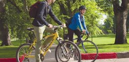 "Photograph of two students riding their bicycles around "" The Oval""."