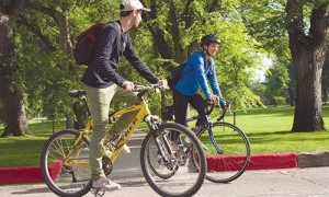 """Photograph of two students riding their bicycles around """" The Oval"""". In the background you can see large sunlit trees and the bright green grass."""