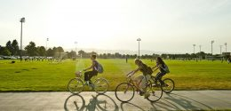 Photograph of three female students riding their bikes on the walkway that goes through the Intramural Fields. The mountains are in the background with the sun high in the sky but more towards the west and their shadows falling towards the camera on the east.