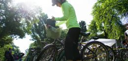 Photograph of a cyclist with her bike helmet and sunglasses on, as she stands next to her bike getting something out of the front basket on her bike. In the background the sun is shining on the tall trees and and you can see a lot of other bikes parked behind her's on the grass.