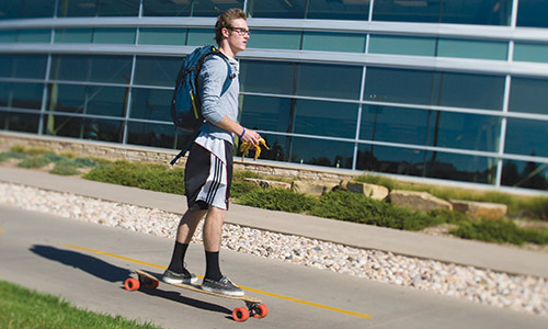 Photograph of a student riding longboard on the bike path that runs just south of the CSU Rec Center.