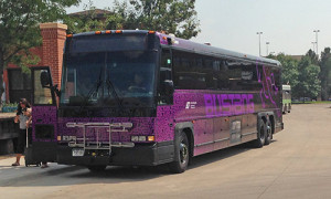 Photograph of a Bustang charter bus parked next to a side walk. A woman with a suitcase appears to have just gotten of the bus.