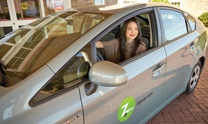 Photograph of a student in a gray Zipcar vehicle. She had her window, is looking out the window and smiling.