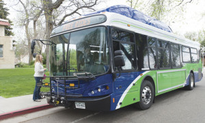 Photograph of a TransFort bus stopped next to a sidewalk on campus. There is a lady about to get on the bus.