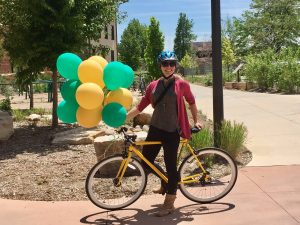 Happy bicyclist standing with balloons