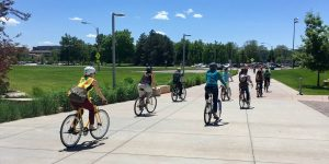 Group riding away from the Rec Center on bikes